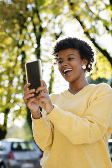 Beautiful black woman with smartphone, outdoor in autumn - MAUF000007