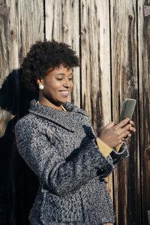 Beautiful black woman using smartphone, outdoor in autumn - MAUF000013