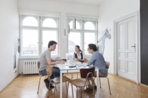 Blurred view of three creative business people having a meeting in a modern office - JUBF000058