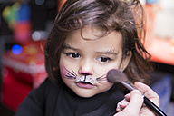 Woman painting little girl's face like a cat - ERLF000080