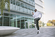 Athlete exercising in front of office building - MADF000590