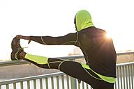 Athlete stretching on bridge railing - MADF000608