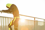 Athlete resting on bridge railing - MADF000611