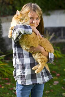 Girl holding tabby cat on her arms - YFF000475