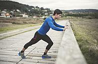 Spain, Ferrol, jogger stretching on a boardwalk - RAEF000668