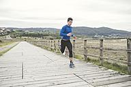 Spain, Ferrol, jogger running on a boardwalk - RAEF000671