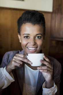 Portrait of smiling young woman sitting in a cafe with cup of coffee - MAUF000022