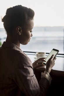 Young woman sitting in a cafe using phablet - MAUF000028