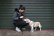 Woman and her dog on a sidewalk in front of a roller shutter - MAUF000038