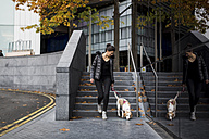 UK, London, woman and her dog walking in the city - MAUF000050