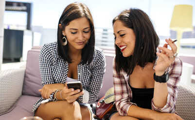Two smiling female friends on terrace looking at cell phone - MGOF001068