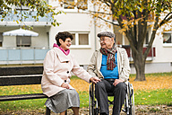Senior woman sitting on bench next to husband in wheelchair - UUF006118