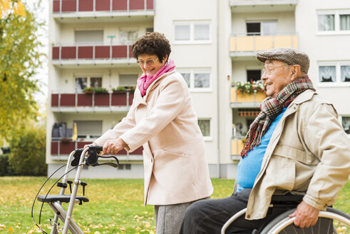 Senior woman with wheeled walker and senior man in wheelchair outdoors in autumn - UUF006124