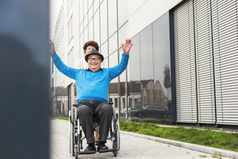 Senior woman with cheering husband in wheelchair on pavement - UUF006130