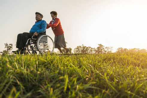 Senior woman pushing husband in wheelchair in the nature - UUF006148