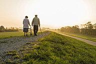 Senior couple walking with walking stick and wheeled walker in the nature - UUF006160