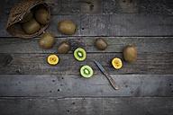 Green and golden kiwis, basket on wood - LVF004173