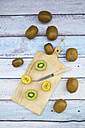 Green and golden kiwis on chopping board, wood - LVF004179