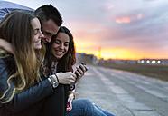 Three happy friends at evening twilight - MGOF001085