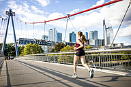 Germany, Frankfurt, young woman jogging on bridge - PUF000437