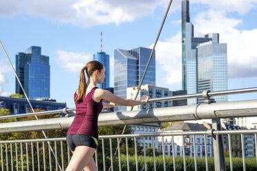 Germany, Frankfurt, young athlete stretching on bridge - PUF000440
