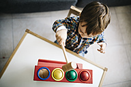 Little boy playing with wooden motor skill toy - JRFF000205