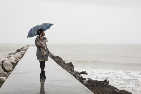 Italy, Grado, woman with umbrella on a rainy day looking at the sea - MAUF000066