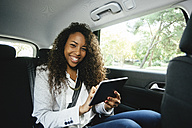 Portrait of smiling young woman sitting on back seat of a car holding mini tablet - EBSF001134