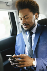 Businessman sitting on back seat of a car looking at smartphone - EBSF001140
