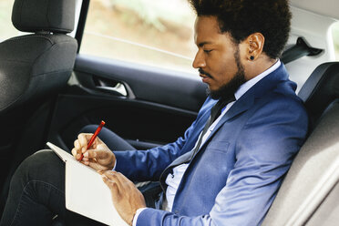 Businessman sitting on back seat of a car writing down something - EBSF001143