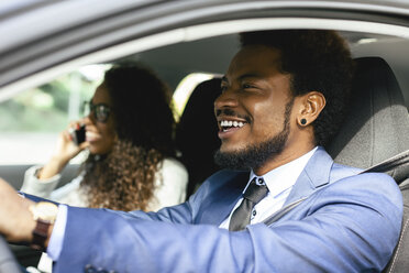 Portrait of smiling businessman driving in a car with his colleague - EBSF001146
