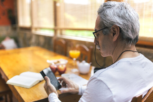 Man sitting at breakfast table using smartphone - MGOF001089
