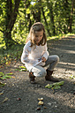 Girl collecting chestnuts on forest track - PAF001478