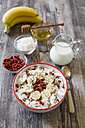 Bowl of muesli with banana slices, chia seeds, coconut chips and goji berries - SARF002325