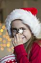Girl with Christmas cap holding cinnamon star - SARF002336