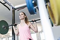 Woman doing barbell squats in a power rack - MADF000708