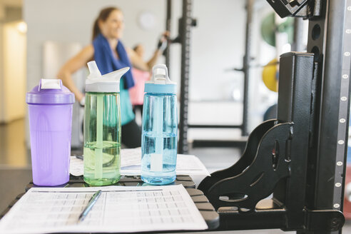 Shaker bottles with woman working out in the background - MADF000747
