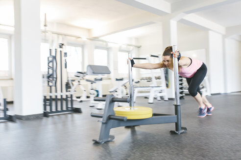 Woman pushing a sled with weights in gym - MADF000753