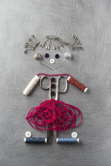 Sewing items building figur of a smiling girl on grey background - MYF001248