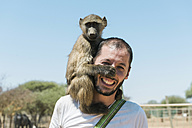 Namibia, man with a baby baboon on his shoulder - GEMF000498