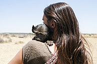 Namibia, back view of woman holding baby baboon - GEMF000501