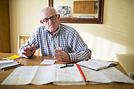 Portrait of senior man with road map planning a trip - RAEF000678