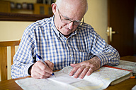 Senior man with road map planning a trip - RAE000684