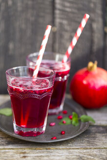 Pomegranate sirup with pomegranate seeds, prosecco and mineral water in glasses - SARF002343