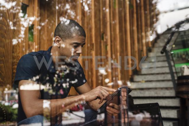 Man using digital tablet behind windowpane - ZEDF000002