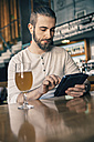 Man using digital tablet in a bar - ZEDF000011
