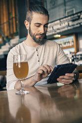 Man using digital tablet in a bar - ZEDF000011