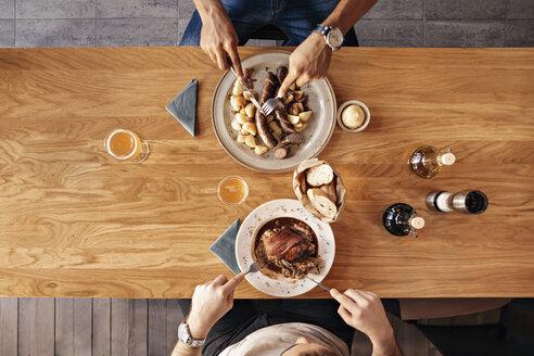 Two men in restaurant having lunch - ZEDF000014