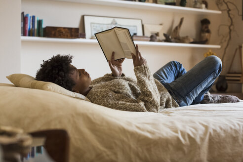 Young woman lying on bed reading a book - MAUF000109