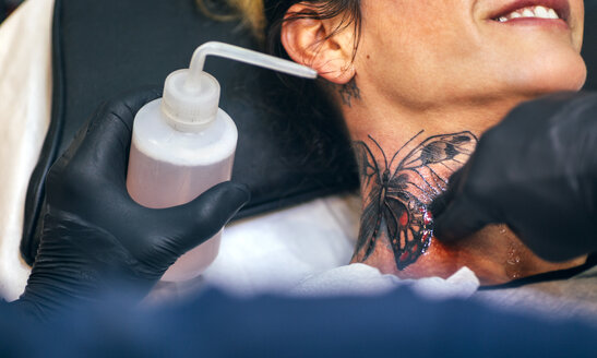 Woman receiving butterfly tattoo at her neck - MGOF001098